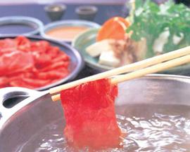 Man lägger i köttet i grytan med ätpinnar
